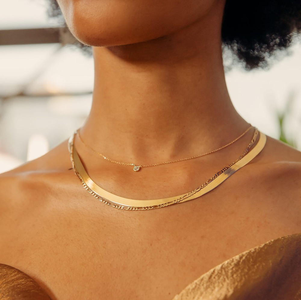 woman wearing three gold necklaces thin and thick chains