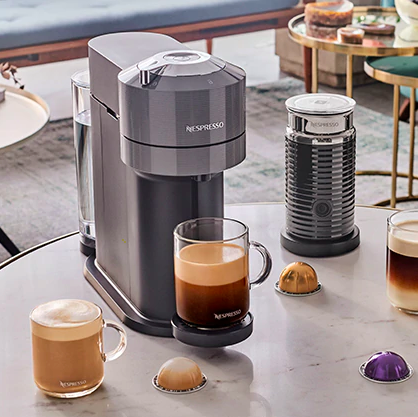 Nespresso coffee machine on table with glass mugs and coffee capsules