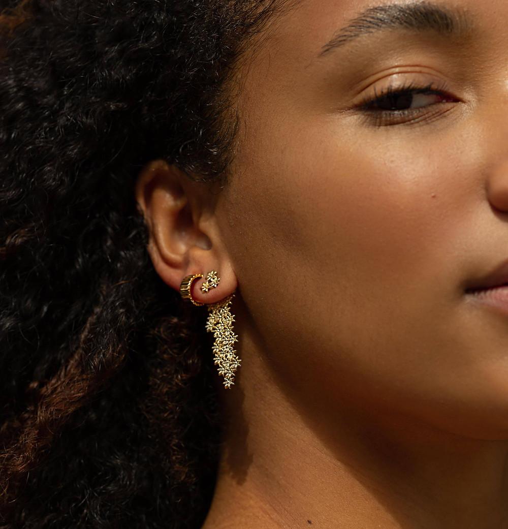 gold flower earrings on ear