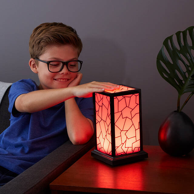 Boy with glasses touching a red glowing lamp