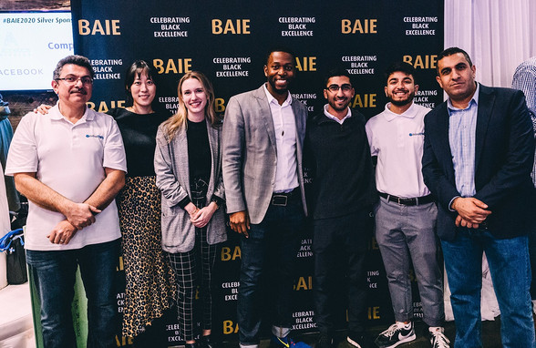 Seven GlobalDWS staff smiling at BAIE 2020 in front of backdrop