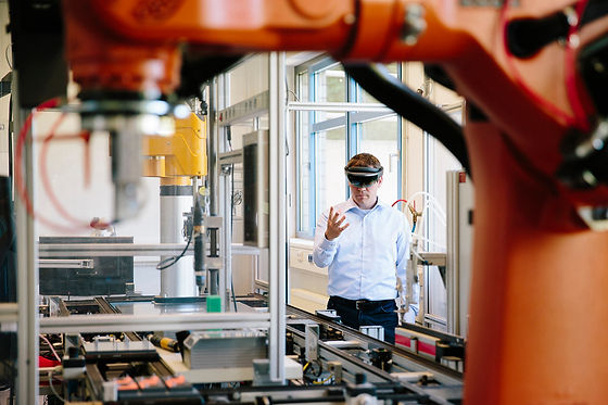 Engineer works with a HoloLens place a virtual robotic arm into the production line.