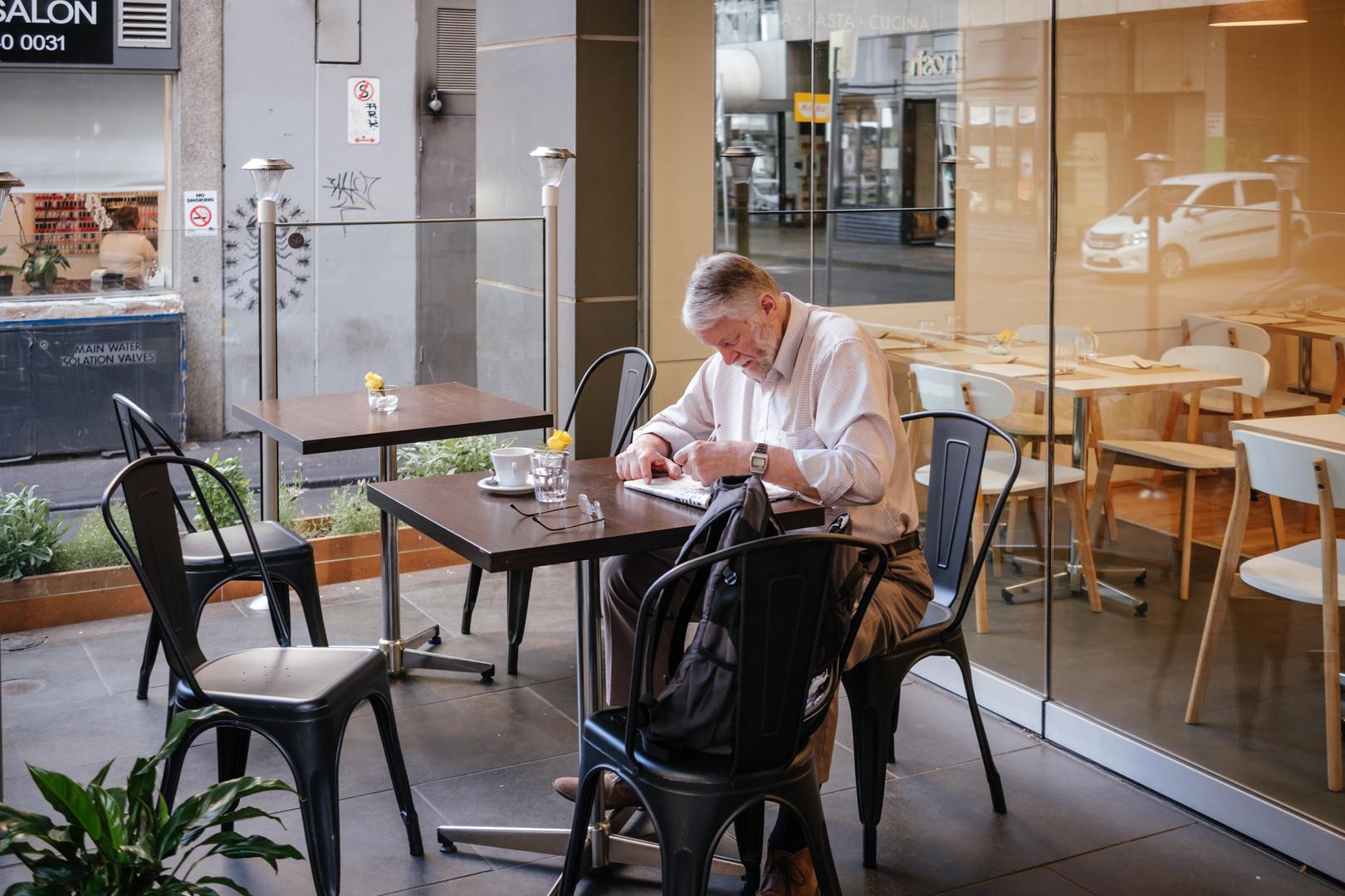 Senior in Cafe writing in Journal