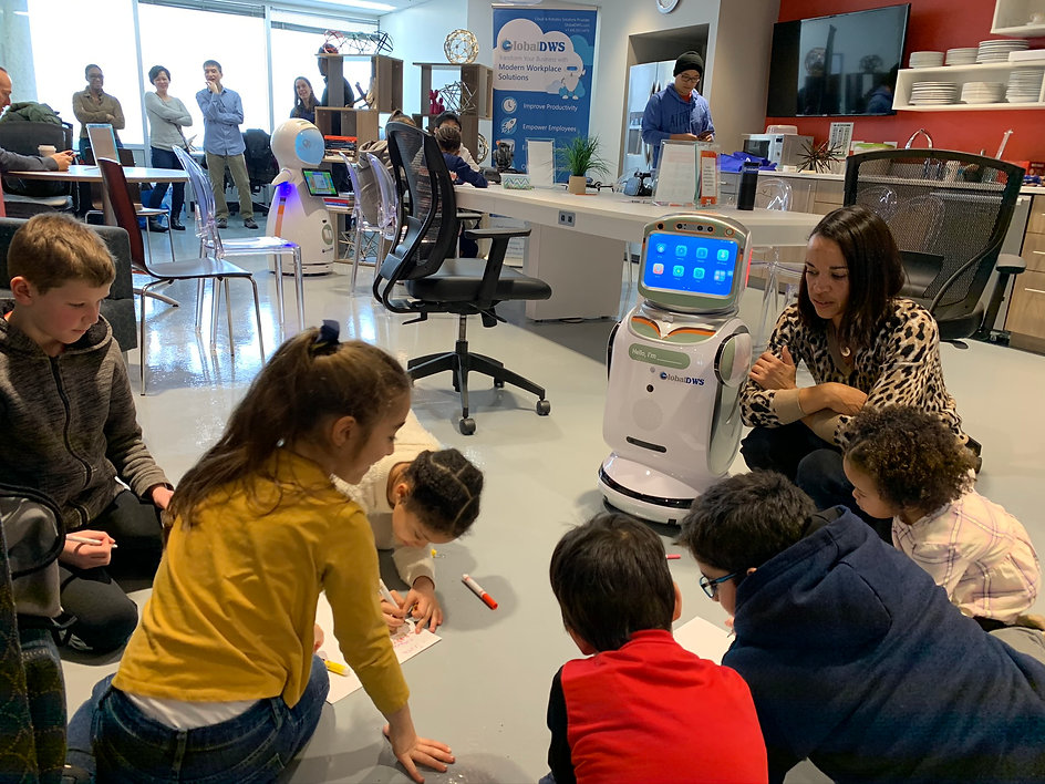 Woman and children sitting on floor with small service robot.