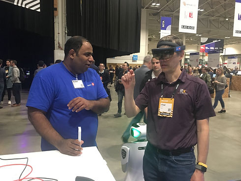 Man in blue shirt assists another man using Microsoft hololens mixed reality headset.