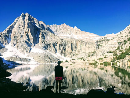woman and dog in front of mountain reflectin on lake