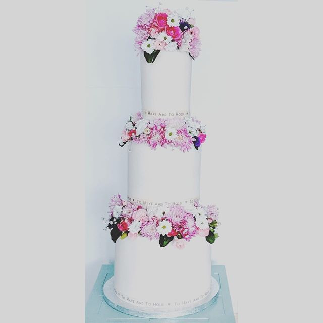 A beautiful white and pink cake focusing