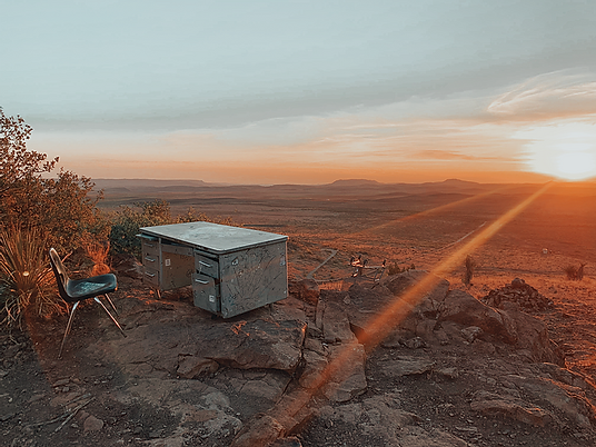 Desk on Hancock Hill in Apline, Texas with rays of setting sun over mountains. Photo credit to 'living for three' blog.