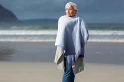 senior-woman-wrapped-in-shawl-at-beach-S