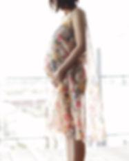 La mujer embarazada en un vestido