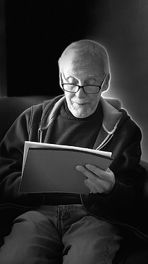 "Black and white photo of ""My Life with Migraine"" author and cartoonist Earle Levenstein reading from a notepad"