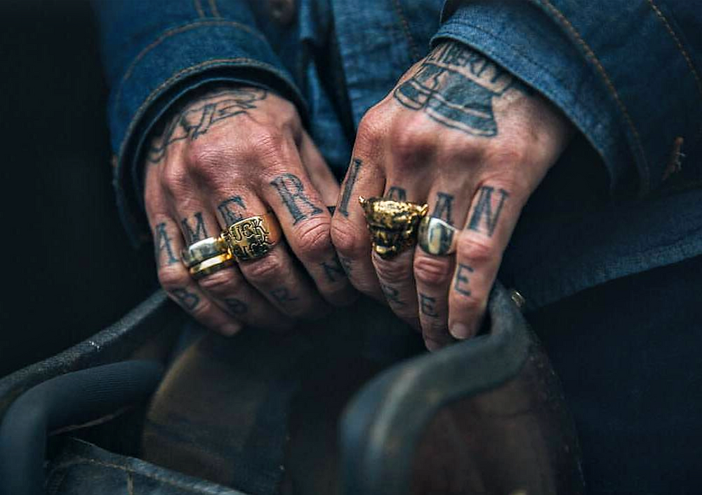 patriotic tattoos on a biker holding a helmet
