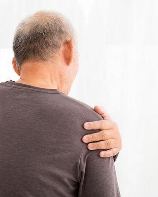 man-holding-his-left-shoulder-in-pain.jp