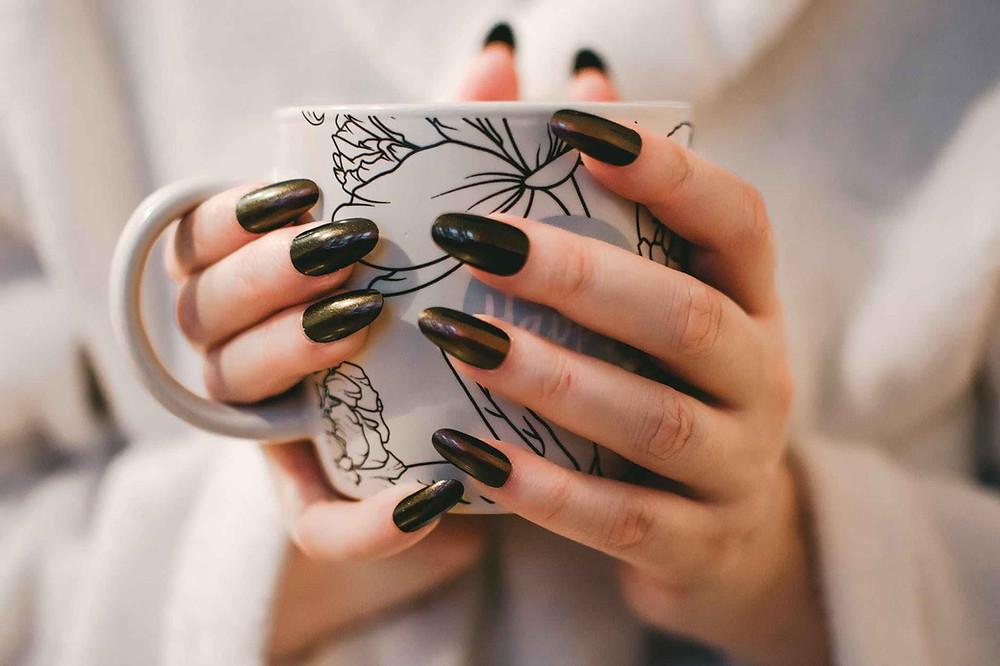 close up photography of a woman in black nail polish holding a mug