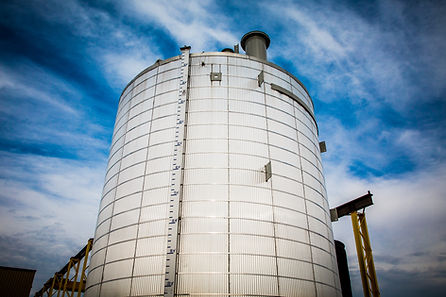 A storag tank against a vibrant blue sky.