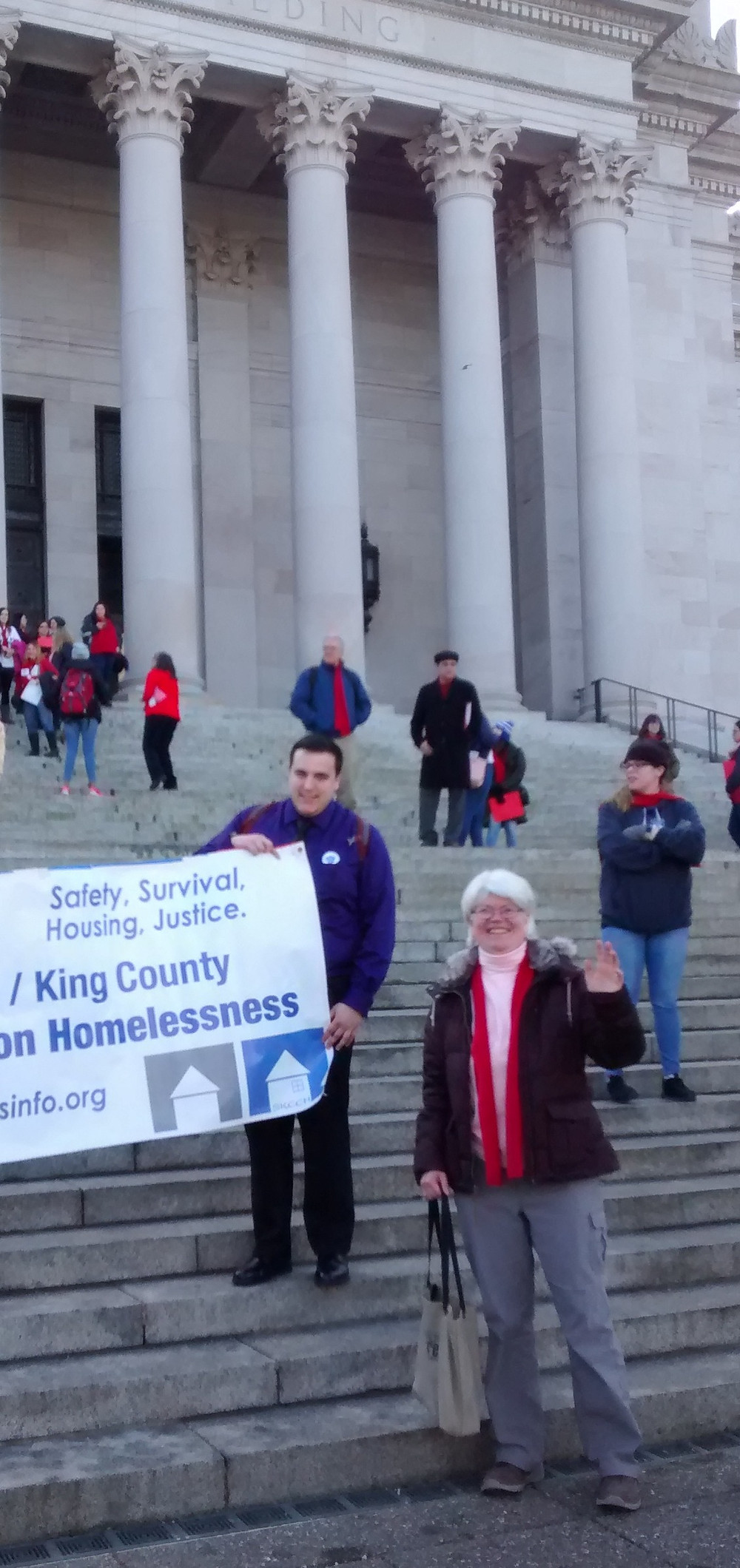 Catherine, wearing a red scarf, stands in front of Washington State's Capitol Building. She is waving and smiling.