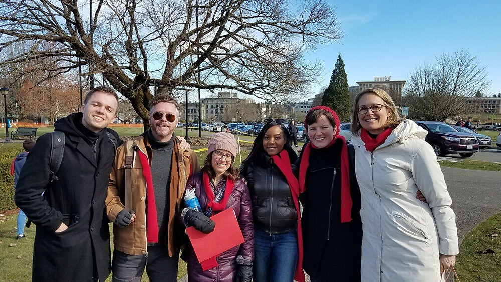 Bellwether Housing staff members wearing red scarves stand in a line smiling at the camera during Advocacy Day 2019.