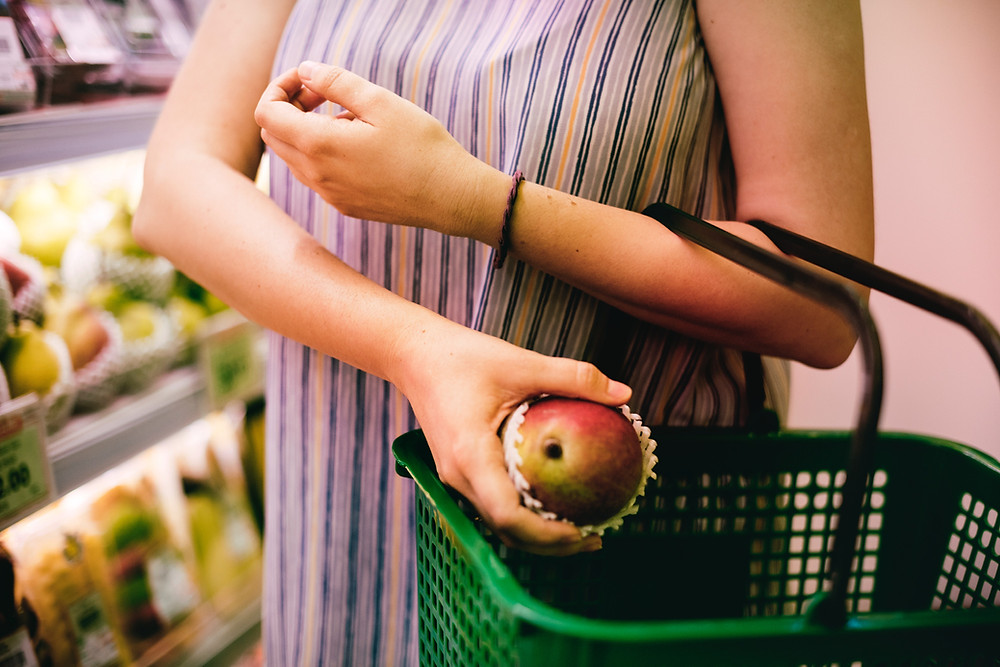 A person in a grocery store places a mango into a green shopping basket.