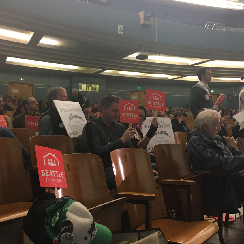 "People in support of the City of Seattle's Mandatory Housing Affordability program hold ""Seattle for Everyone"" signs during a public hearing in District 4"