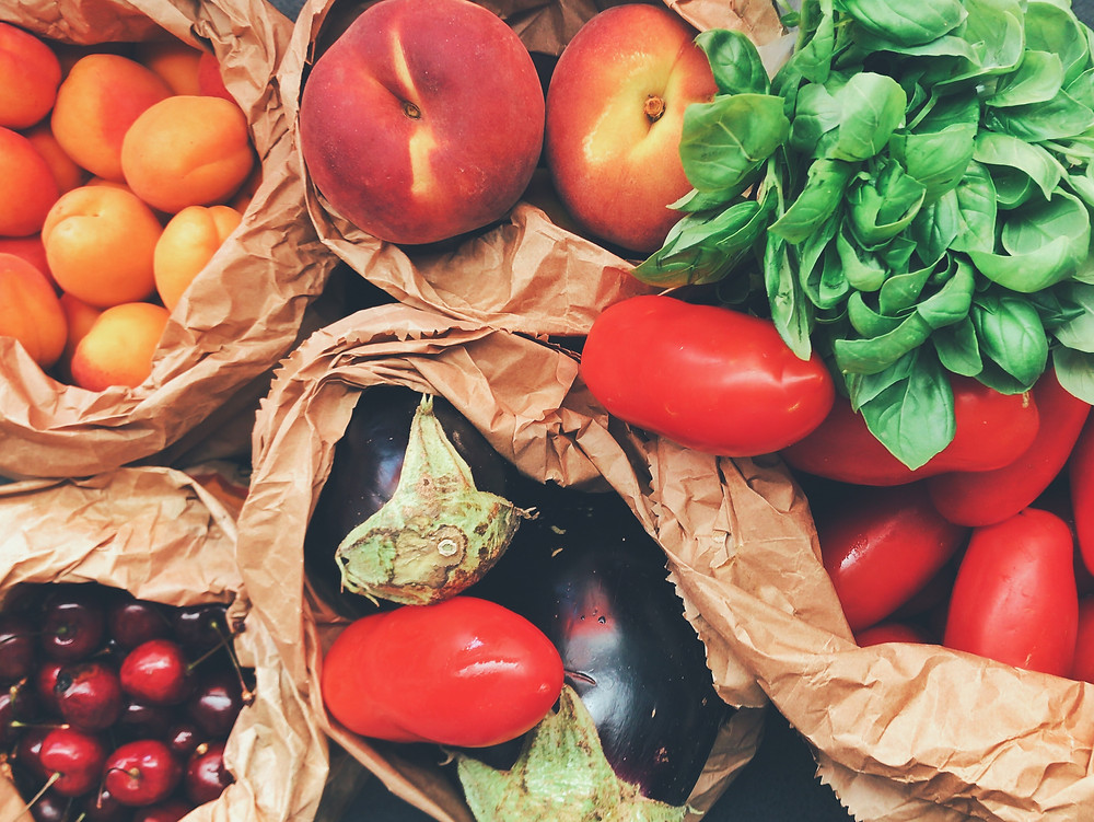 Apricots, peaches, basil, tomatoes, eggplant, and cherries are shown in brown paper shopping bags.