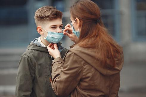 Femme avec un masque qui met un masque à un enfant