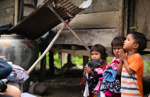 Three children receiving clothes from TASSEL volunteers.