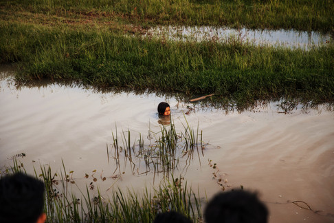 A TASSEL student swimming in a river looking for snails and other creatures. Many Cambodians use this as a source of food as well as an item to sell for money.