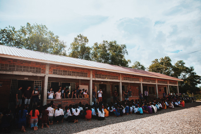 Students in the Samrang School sit in the shade as the foreigners address them before a week of studying.