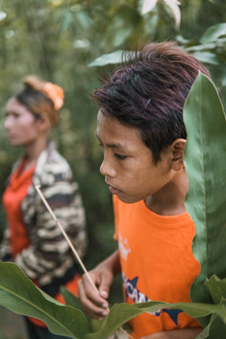 A TASSEL student walking through head high weeds towards a river where he'll gather water for drinking.