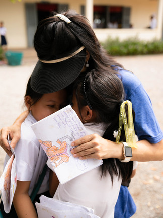 Teacher Ella hugs two students after receiving drawings from them.