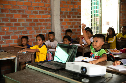 A student in the Samrang school raises his hand to volunteer to read the word on the board aloud.