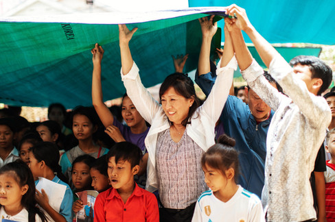 Khmer teachers and TASSEL volunteers hold up a tarp to provide shade for the students.