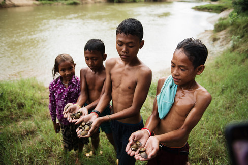 4 children hold up their findings after searching for food in the river.