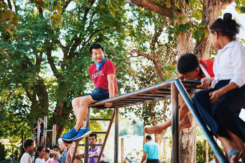 Teacher Ray sits on the monkeybars in the schoolyard during freetime and encourages the students to join him.