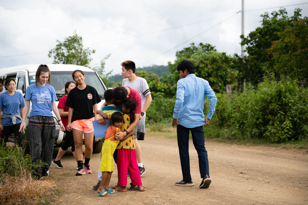 TASSEL volunteers arrive at Samlot Village and Teacher Joji is greeted by 3 children.