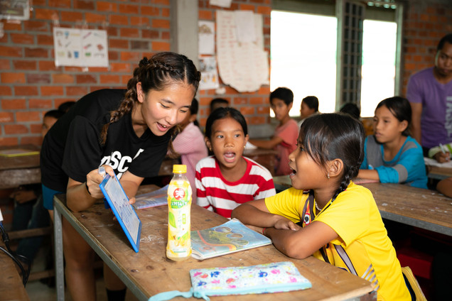 TASSEL volunteer teaching the students English during a summer visit.
