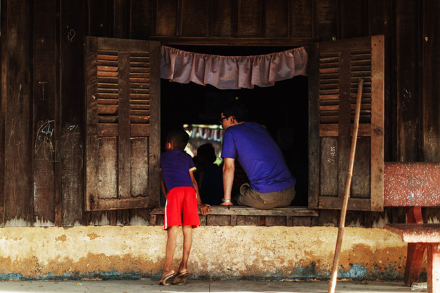 A TASSEL volunteer and a young boy observe a class through the window.
