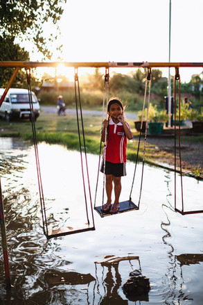 A TASSEL student plays on the swings after a storm.