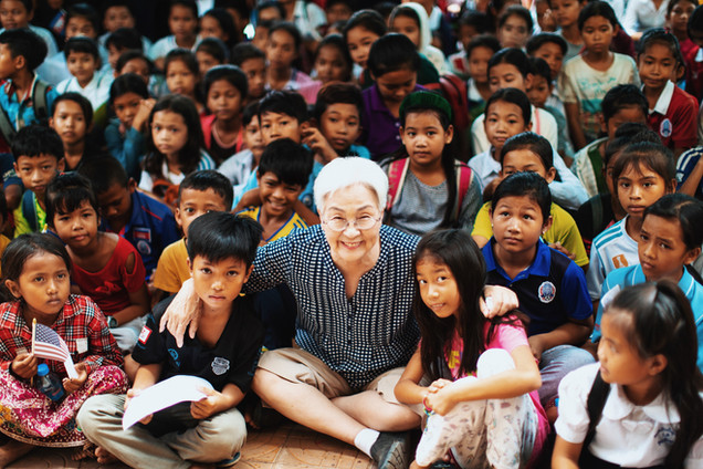 Grandma (volunteer) sitting with students of the Rattinak Tassel School.