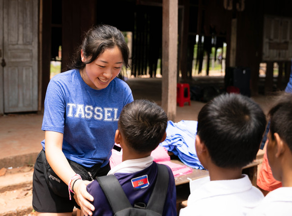 A TASSEL volunteer holds up a shirt to a student.