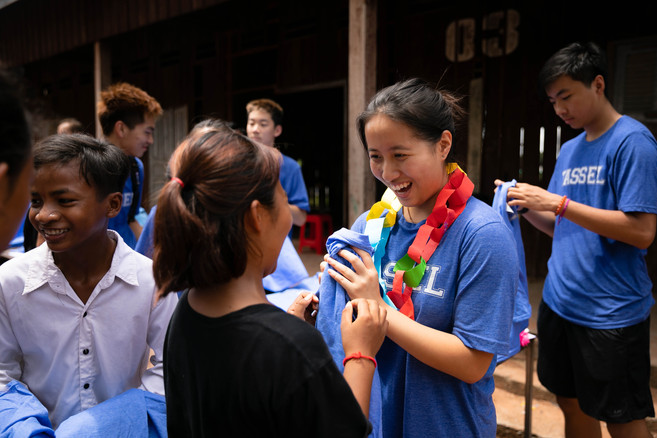 A TASSEL volunteer gives a TASSEL shirt to a student.