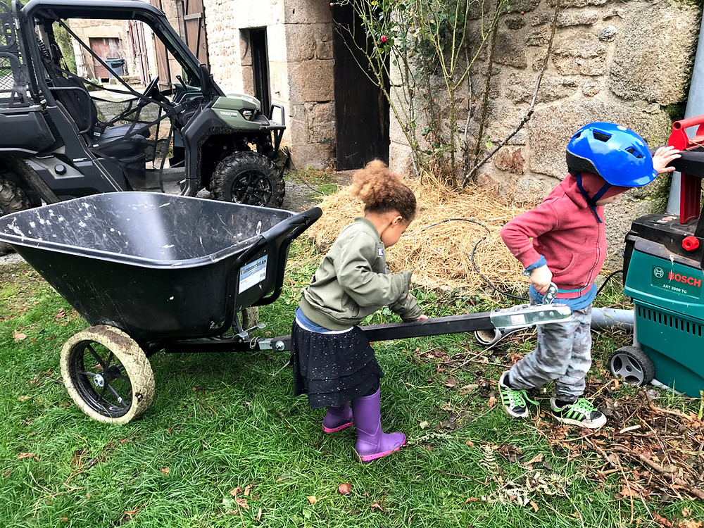 The kids are putting a Hammerlin towable wheelbarrow in position to receive wood mulch from the broyeur.