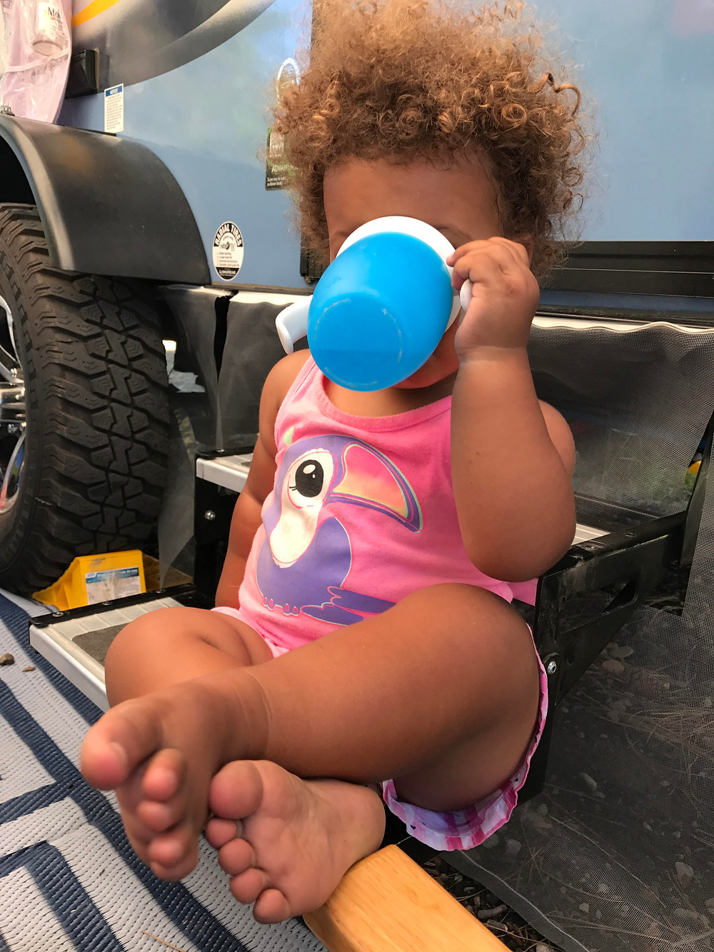 Toddler chilling at a campsite drinking water
