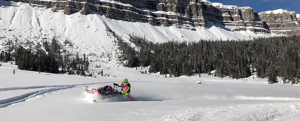 Snowmobiler in snowy mountain landscape at Brooks Lake Lodge, an all-inclusive luxury resort near Yellowstone