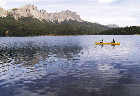 People in a canoe at Brooks Lake Lodge, an all-inclusive luxury resort near Yellowstone