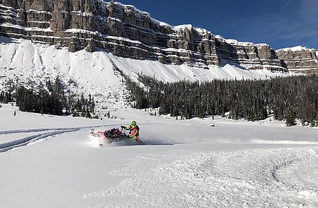 Snowmobiler in snowy landscape at Brooks Lake Lodge, an all-inclusive luxury resort near Yellowstone