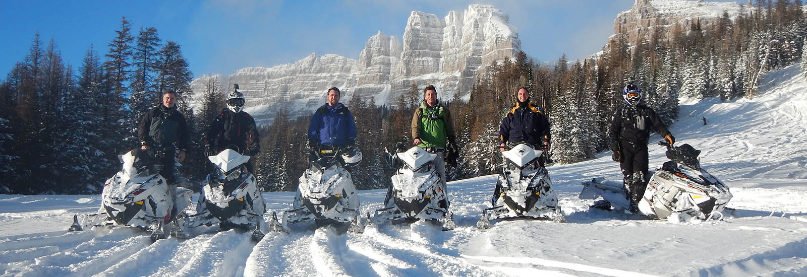 Snowmobilers in a snowy mountain landscape at Brooks Lake Lodge, an all inclusive resort in Dubois, WY