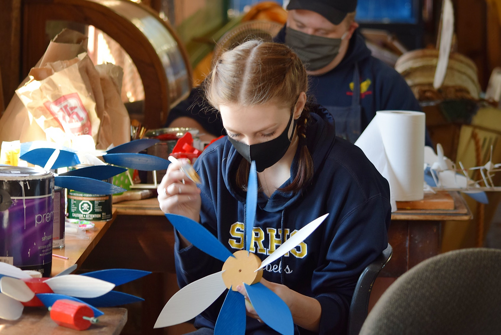 Summer students paint flower-shaped whirligigs in the Dory Shop Museum, in Shelburne, Nova Scotia.