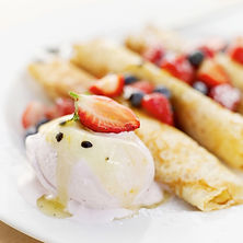 Delicious dessert crepes topped with fresh berries and ice cream