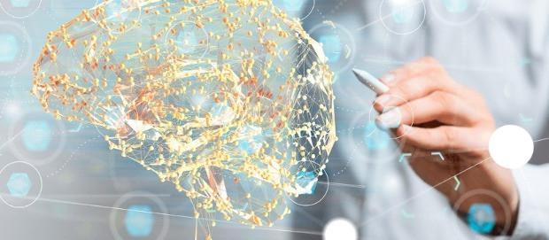 mão esquerda segurando uma apple pen apontando para um cérebro de conexões tecnológicas nas cores amarelo e laranja.